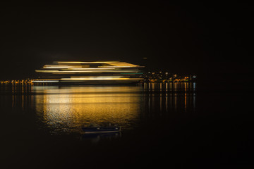 Sea cruiser with lights reflecting on the water