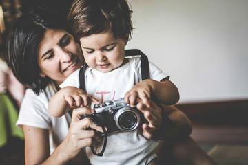 Madre e hija juegan con una camara de fotos