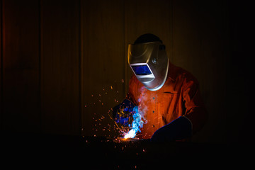 Welder with personal protective equipment and protective mask welding steel pipe in industrial factory