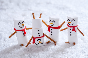 Happy funny marshmallow snowmans on snow Wall mural