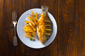 fried fish with fries on a white plate on a wooden table