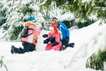girls playing with snow in the winter forest. Girls in ski suits shape snowman,  girl having fun with snow in winter outdoors. Mother and daughter girl playing in the snow. Happy people in winter