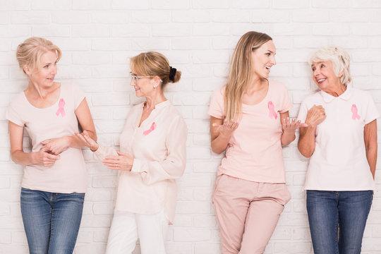 Women standing beside white wall