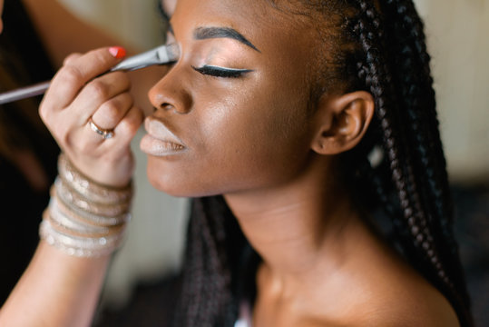 Make up doing make up to african black woman. Beautiful model with braiding.