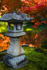 Traditional stone lantern and red maples in a Japanese garden during autumn