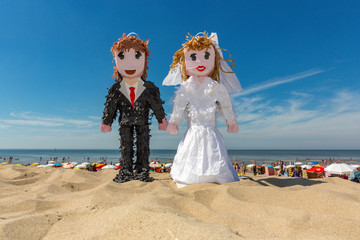 Pinata man and woman doll on the beach in Noordwijk Holland