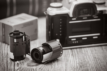 Old film camera and roll films on the wooden background. Low depth of field.