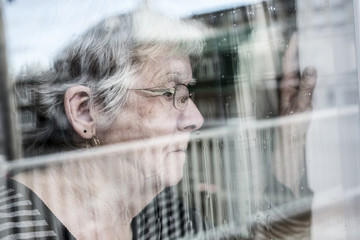 Senior woman looking out through a window like depress Wall mural