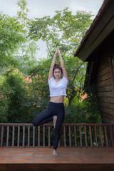 Women Relaxing In Yoga Tree Pose On Wooden Terrace