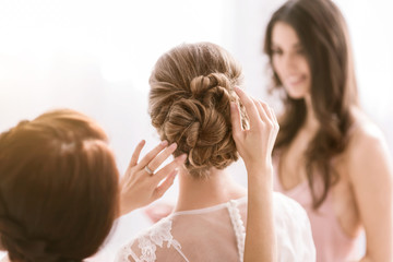 Pleasant bridesmaids helping the bride with her hairstyle