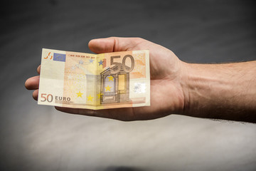 fifty euro banknote in male hand close up. Male hand holding a 50 euros
