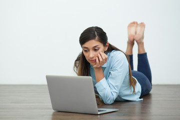Serious Woman Lying on Floor and Working on Laptop