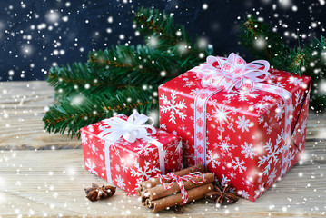 Christmas gifts with cinnamon on dark background.