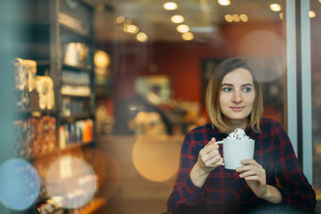 Portrait of young beautiful girl enjoying flavoured coffee in cozy cafe, Hipster girl resting after autumn walk in cozy cafe, Autumn mood, Christmas mood