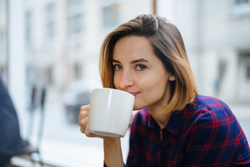 Young beautiful woman sitting in comfortable coffee shop during work break, Portrait of a young beautiful women enjoying coffee during morning breakfast