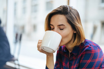 Portrait of a young beautiful businesswomen enjoying coffee during morning breakfast, Mock-up of cup of coffee, Young beautiful woman sitting in comfortable coffee shop during work break