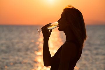 portrait de femme en contre-jour sur la plage avec une coupe de champagne