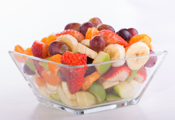 Fruit salad in rich colors in a glass bowl, on light background