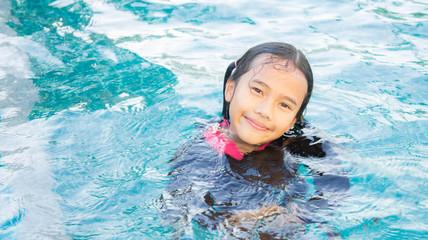 The baby girl asian enjoy swiming , kid girl playing swiming , y