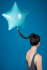 Star shaped balloon attached to plaited hair, artwork