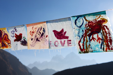 Childish painting of red pigeon hand drawn on white cloth. Hand painted flags waving on a bright sunny day. Love and peace concept expressed by children in Himalayan village of Thame, Nepal.
