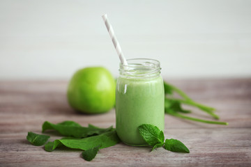 Glass jar with delicious apple milkshake on wooden table