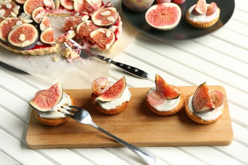 Delicious fig tarts and cake with almond flakes on table