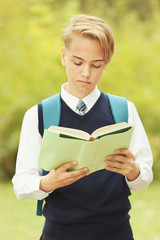 Handsome teenager with book in park