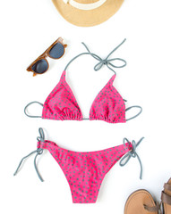 Summer outfit, beach outfit, summer stuff. Pink polka dot swimsuit, retro sunglasses, straw hat. Flat lay, top view