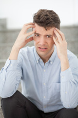 Stressed businessman holding head with hands