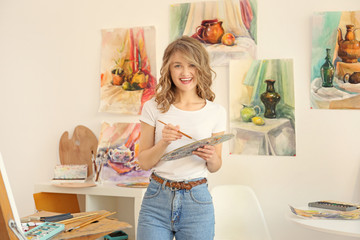 Young female artist with brush and palette in studio