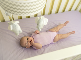 Infant Baby in Purple Crib with Elephant Mobile Smiling at Camera