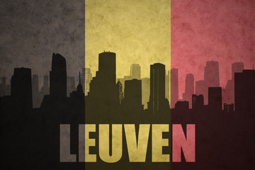 abstract silhouette of the city with text Leuven at the vintage belgian flag