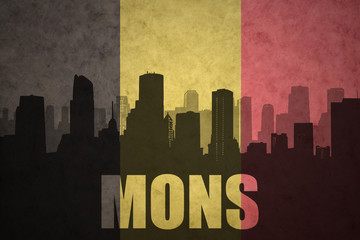 abstract silhouette of the city with text Mons at the vintage belgian flag