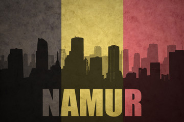 abstract silhouette of the city with text Namur at the vintage belgian flag