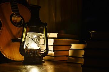Luminous kerosene lamp, guitar and books on the table