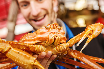 Seller man trader on fish market, keep in hand and show alive big giant crab to customers and smile. Crab kind of crawfish live in ocean and sea and very useful and dietician and delicious food.
