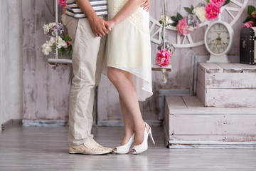 Legs pretty young loving couple on the wall with bouquet in vintage scenery. Love, wedding concept.