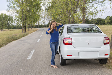 Young woman using her smart phone next to a broken down car