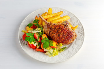 Grilled pork cutlet meat garnished with potato and salad on black table