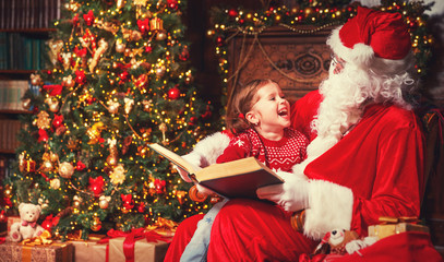 happy child girl with Santa reading book