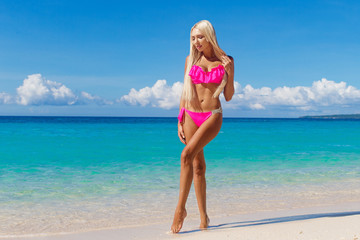 Beautiful blonde with long hair in bikini having fun on a tropical beach. Blue sea in the background. Summer vacation