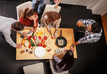 Young group of friends in kitchen preparing together vegetarian meal.Cutting vegetables.