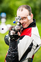 Man sport shooting. Smiling man on free rifle triaining