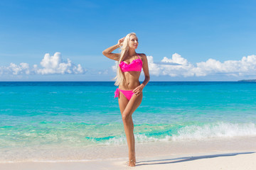 Happy beautiful young girl in bikini on a tropical beach. Blue s