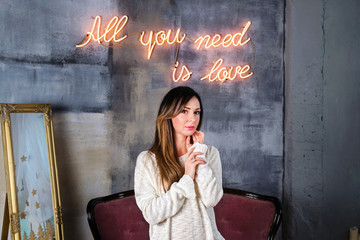 Young brunette woman in a cozy sweater standing in front of All you need is love neon sign on a background