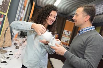 woman pouring man tea in tea shop