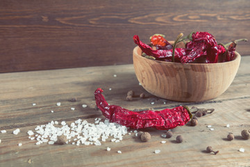 Dried chili peppers in a wooden bowl, salt and pepper on dark wooden table
