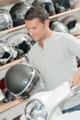Man holding crash helmet and handlebar of scooter
