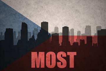 abstract silhouette of the city with text Most at the vintage czech republic flag
